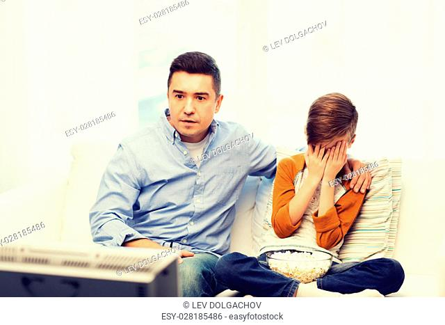 family, people, technology, television and entertainment concept - scared father and son watching horror movie on tv at home