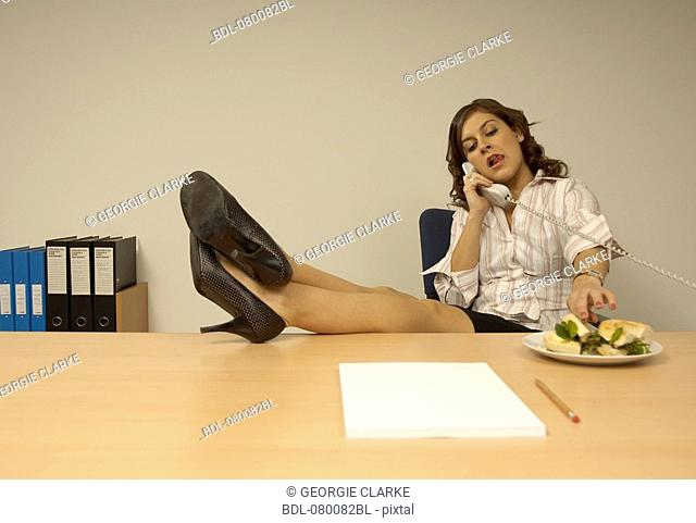 secretary sitting at desk talking on the telephone with her legs up