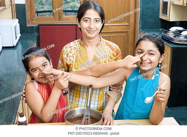 Portrait of a mid adult woman baking chocolate sauce with her daughters touching each other''s nose
