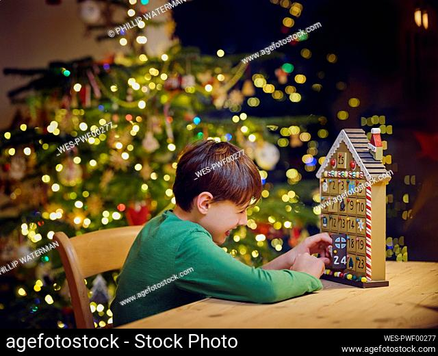 Playful boy opening advent calender door during Christmas at home