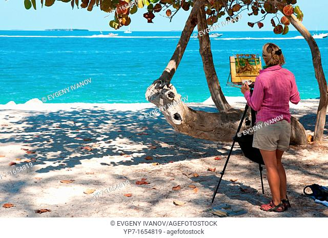 Woman painting a piece of art on the beach of Key West, Florida