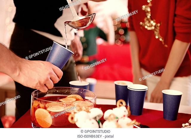Cropped shot of young man serving punch to friends at christmas party