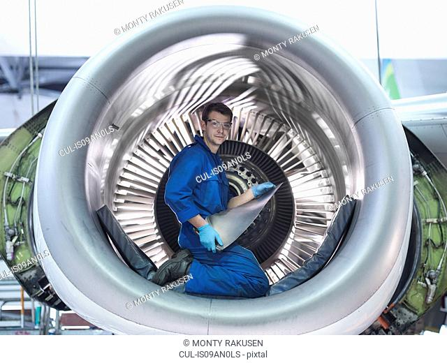 Engineer holding jet engine turbine blade in aircraft maintenance factory, portrait