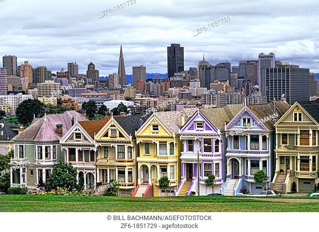 Famous Victorian House row and skyline with Transamerica Building in San Francisco California