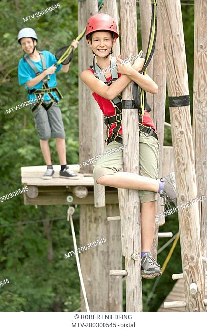 Portrait of boy and girl climbing crag, smiling