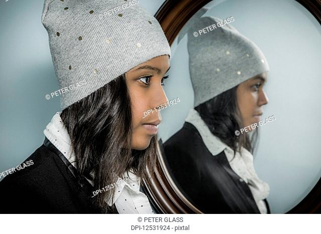 Young hispanic woman wearing a knit hat with her reflection in a mirror; Connecticut, United States of America