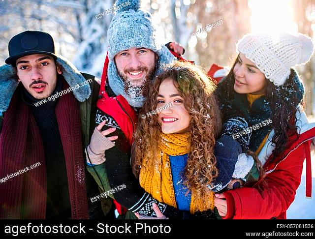 A group of young cheerful friends on a walk outdoors in snow in winter forest, looking at camera