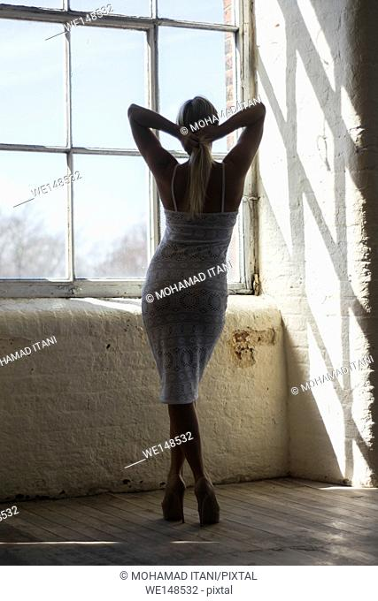Full length silhouette of a woman standing by the window