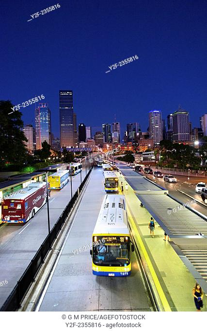 people and buses at South Bank bus stop with Brisbane city skyline at dusk