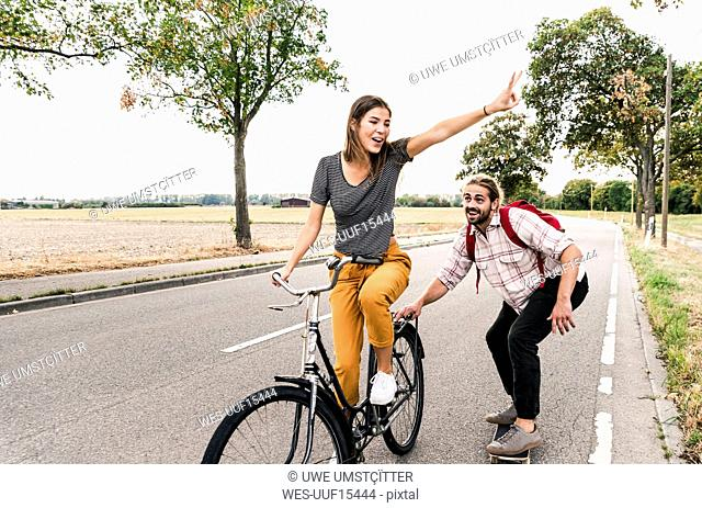 Happy young couple with bicycle and skateboard on country road