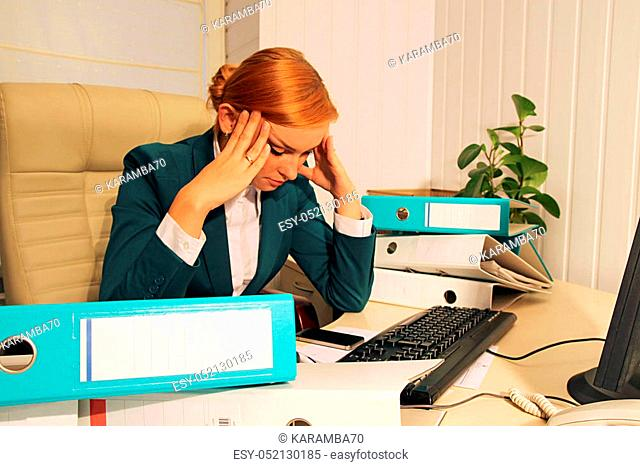 Portrait of exhausted, stressed, depressed, concentrated young woman sitting in chair at desk in her office with stack of folders holding her hands at temples