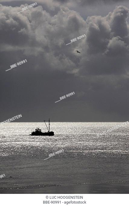 Dark clouds over the Wadden Sea, with a small fishing boat, grey tones