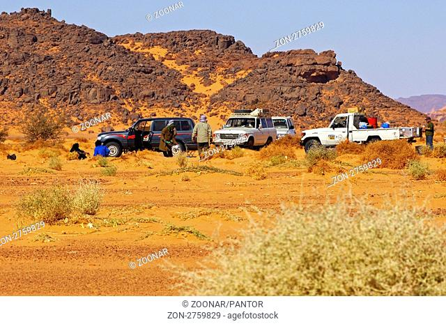 Geländewagen einer Expedition an einem Sammelpunkt im Akakus-Gebirge, Sahara, Libyen / Off-road vehicles of an expedition at a meeting point in the Acacus...