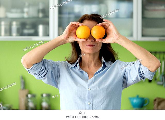 Mature woman covering her eyes with oranges in kitchen at home