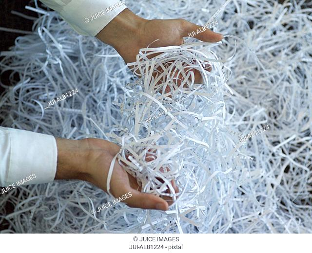 Businessman holding bunch of shredded paper