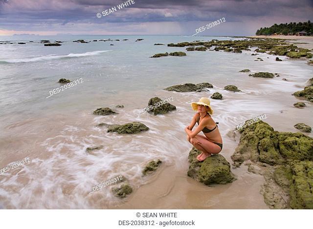 A Woman Tourist Crouches On A Rock On The Beach On A Tropical Island, Koh Lanta Thailand