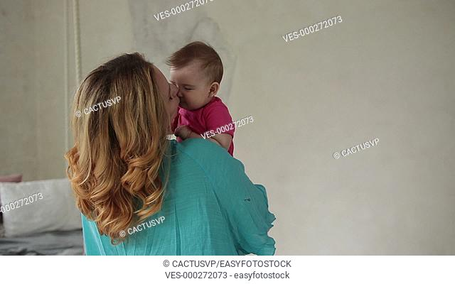 Loving mom kissing cute baby girl's nose