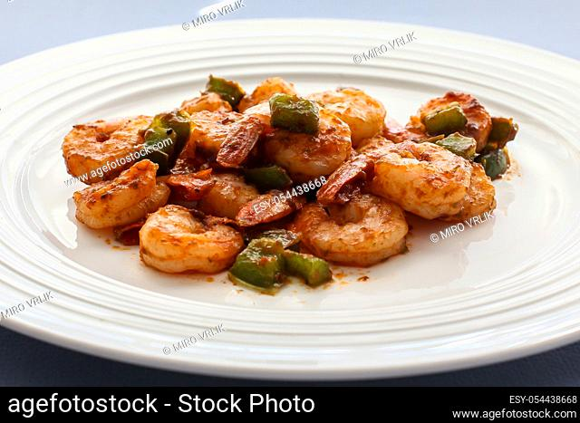 Shrimps with green belly peppers on white plate