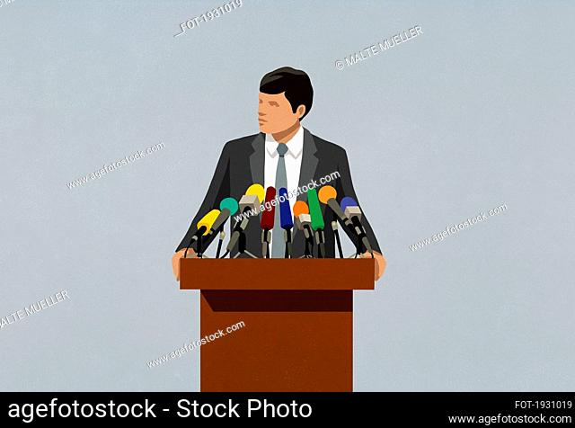 Politician speaking at microphones on podium