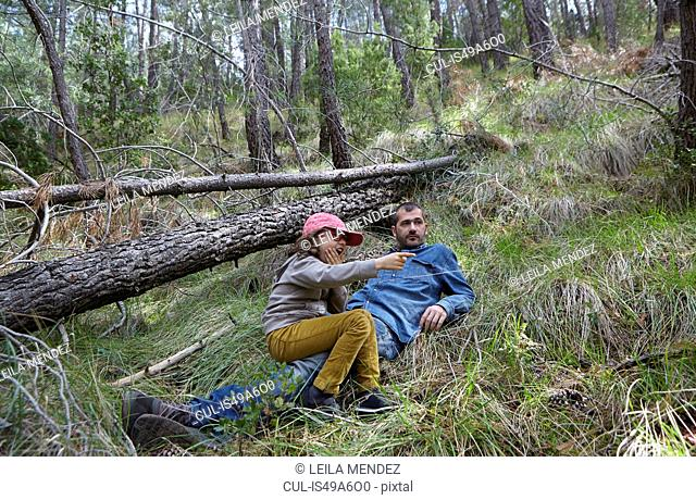 Mid adult man relaxing with daughter in forest
