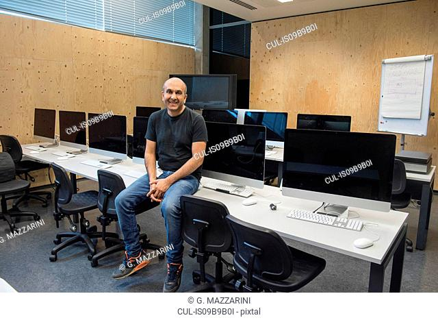 Man sitting on desk in computer room looking at camera smiling