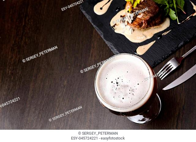 Beer glass and steak on black table, view from above
