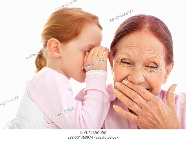 Portrait of sweet girl telling a secret to her grandmother