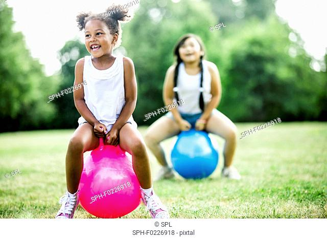 Girls bouncing on inflatable hopper