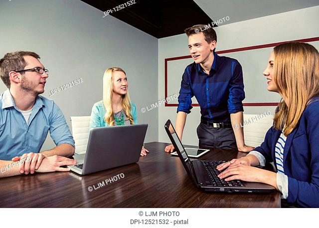 Young millennial businessman speaking to a group of young professionals in a conference room in a place of business; Sherwood Park, Alberta, Canada