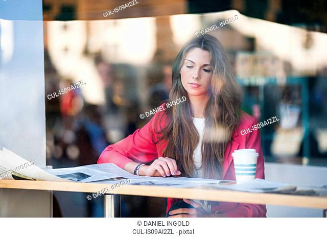Young woman sitting in window with coffee, reading newspaper