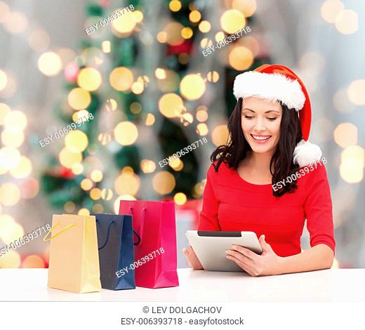 holidays, technology and people concept - smiling woman in santa helper hat with shopping bags and tablet pc computer over christmas tree with lights background