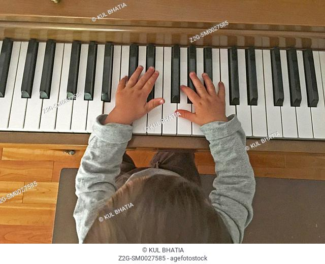 A 15 month old child tries out the keyboard of a piano, Halifax, Nova Scotia, Canada