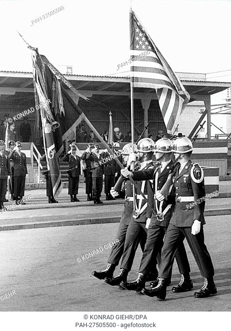 American soldiers marching past an honor tribune, with the US flag and the flag of the battalion, during a parade on 15 October 1965 in Berlin-Lichterfelde