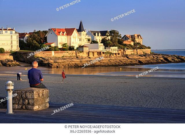 Man sat on wall enjoying evening sunshine at Conche de Saint Palais near Royan