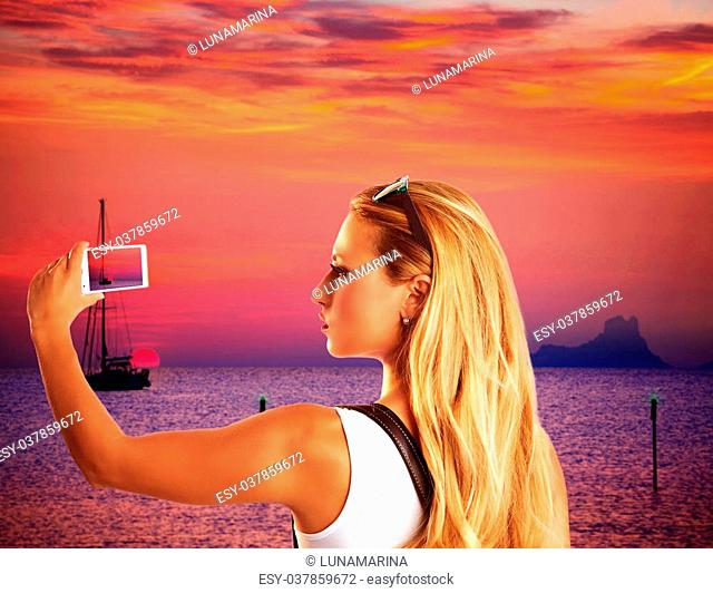 Blond tourist taking photograph sunset with smartphone in Formentera photomount