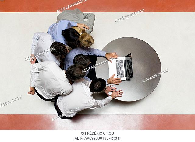 Business associates staring at laptop computer in disbelief