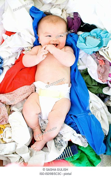 Overhead portrait of baby girl lying amongst laundry