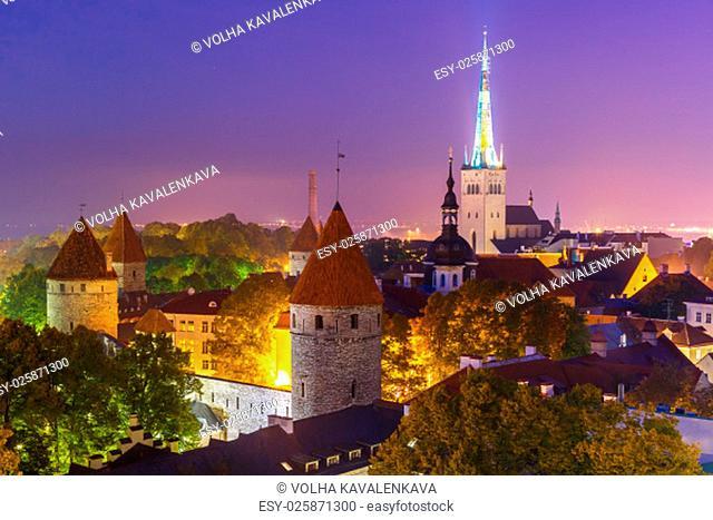 Aerial cityscape with Medieval Old Town, St. Olaf Baptist Church and Tallinn City Wall illuminated at autumn night, Tallinn, Estonia