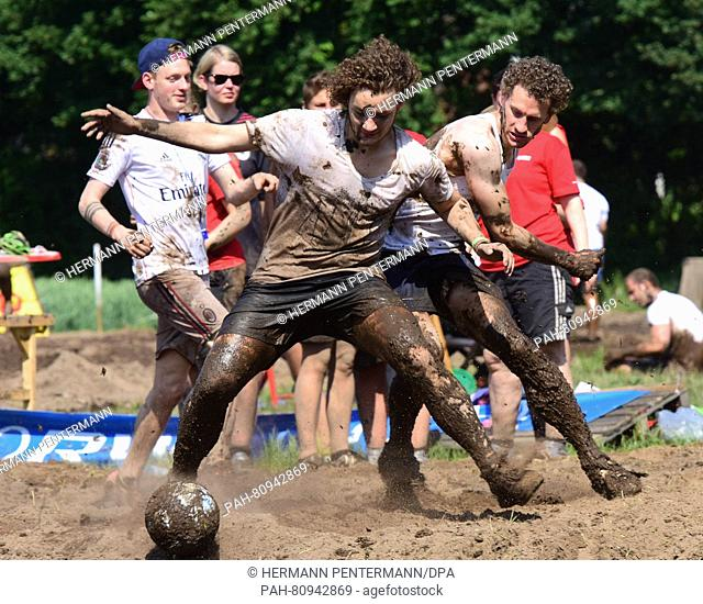 """Players from the teams """"""""Sauf Dortmund Schlamm"""""""" and """"""""Sparta Lattenstramm"""""""" from Stuhr compete for the ball during the German swamp football championships in..."""