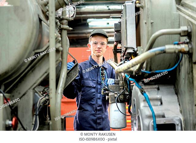 Portrait of young apprentice locomotive engineer in train works