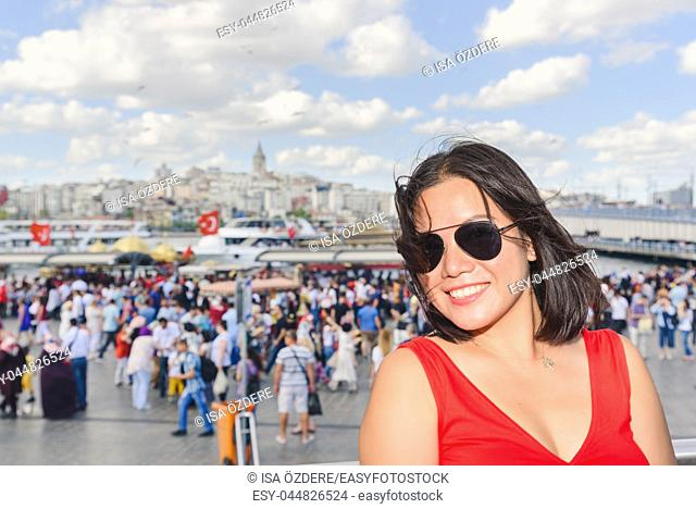 Beautiful Chinese woman poses with view of Galata Tower at Eminonu district in Istanbul, Turkey