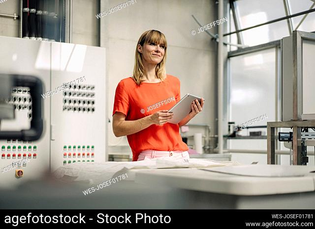Female entrepreneur with digital tablet standing at table in greenhouse