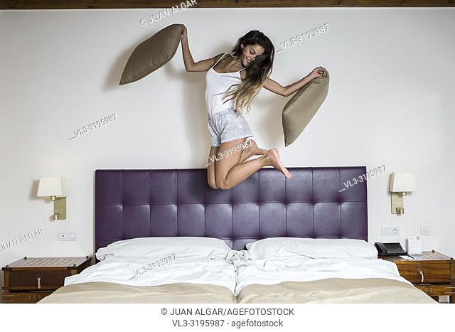 Excited slim woman with pillows jumping on bed in hotel room having fun and laughing