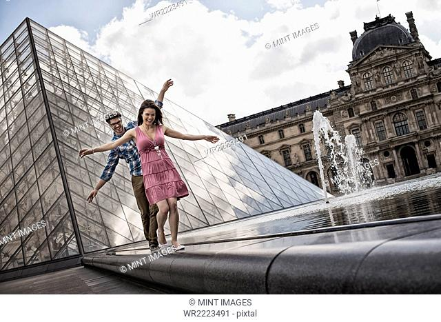 A couple in the courtyard of the Louvre museum, by the large glass pyramid. Water jets and shallow pool