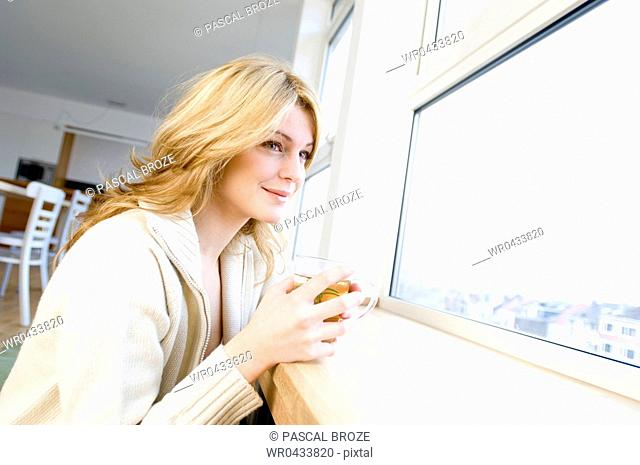 Side profile of a young woman holding a cup of herbal tea