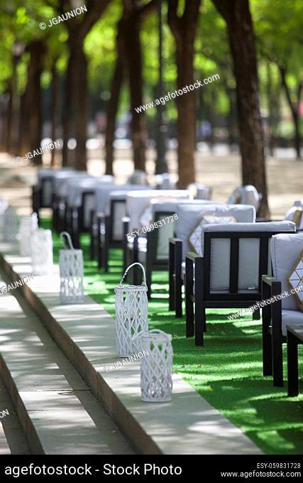 Outdoors restaurant terrace along public park, Spain. Public spaces for business