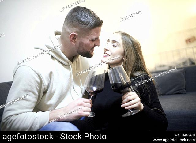 couple with wine glasses on couch feeling inclination towards each other