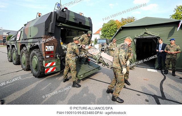 27 August 2019, Saxony, Frankenberg: Soldiers recover an injured comrade with a GTK boxer with medical equipment during a demonstration in the Wettin barracks