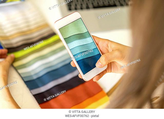 Fashion designer taking pictures of fabric samples with ger mobile phone