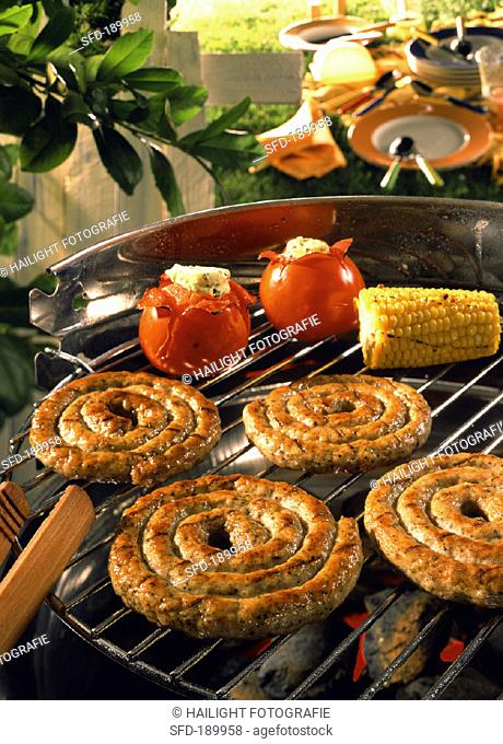Barbecue scene with sausages and vegetables on the barbecue